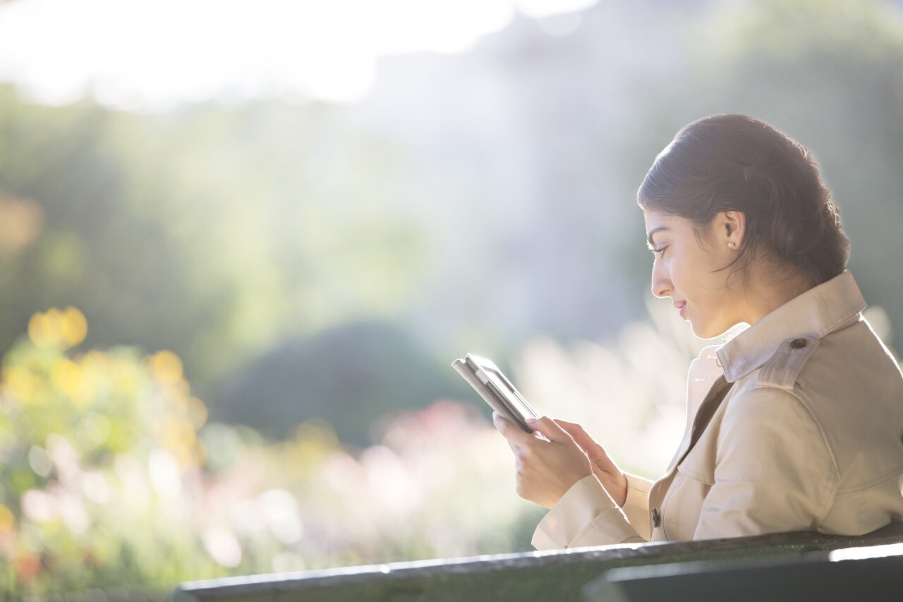 Businesswoman using digital tablet in park